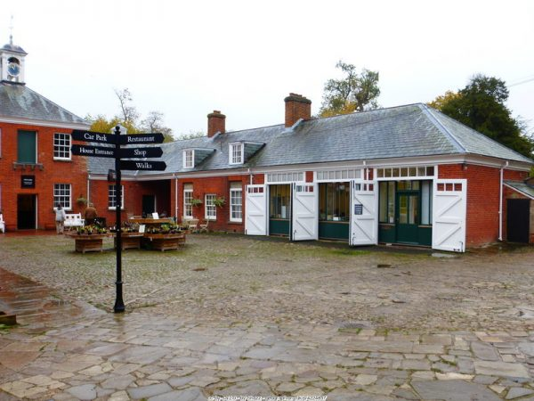 Old stable yard with a black signpost at Hatchlands Park, in a stone flagged courtyard of traditional red brick buildings with grey slate roofs, white painted stable doors open to reveal rooms converted inside (cc-by-sa/2.0 - © Shazz - geograph.org.uk/p/4224857)