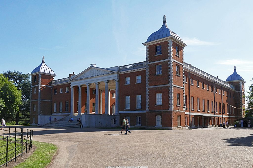 The grand Osterley Park House under blue skies, viewed from the front corner, showing the majestic towers and columned entryway. (cc-by-sa/2.0 - © Alan Hunt - geograph.org.uk/p/4600503)