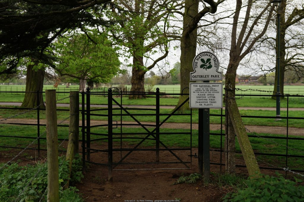 A distinctive National Trust boundary sign for Osterley Park, next to a kissing gate, looking through trees across the main drive (cc-by-sa/2.0 - © Peter Trimming - geograph.org.uk/p/4911050)